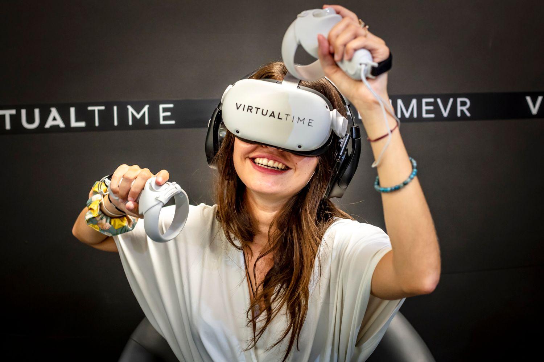 Une joueuse teste une expérience de tir à l'arc dans un box de Virtual time