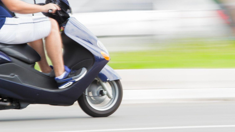 Au volant de son scooter et avec son fils à l'arrière, un homme...