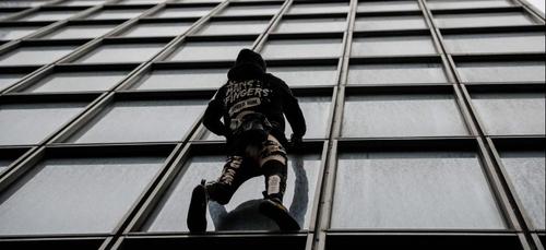 Le Spiderman français grimpe la tour Total de la Défense à mains...
